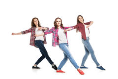 Three young women dancing over white background Stock Image