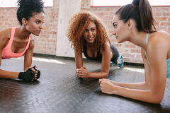 Three young women doing pushups stock images