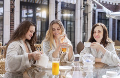 Three young women drinking tea at spa resort Royalty Free Stock Photo