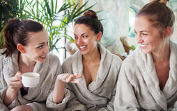 Three young women drinking tea at spa resort Stock Image