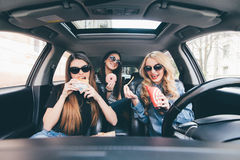Three young women drive a car, speaking each other and eating a fast food in a car in traffic jam. Three young women drive a car, speaking each other and eating Stock Image