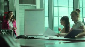 Three young women ending the conference in the office. Two beautiful girls sitting on the table and pick up the documents on the table. The general manager stock footage