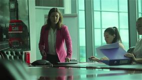 Three young women ending the conference in the office. Three young women working in the office. Two beautiful girls sitting on the table and pick up the stock footage