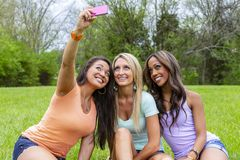 3 Girlfriends Enjoying A Day At The Park While Taking Selfies stock images