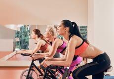 Three Young women on exercise bikes at gym Stock Photos
