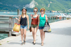 Three young women go shopping Royalty Free Stock Image