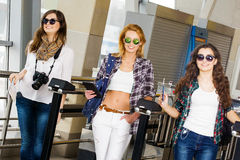 Three young women go through the turnstile at the station or at the airport. Europeans. Gathered in a guided tour.Three. Three young women go through the Stock Image