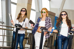 Three young women go through the turnstile at the station or at the airport. Europeans. Gathered in a guided tour.Three. Three young women go through the Stock Images