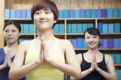 Three young women with hands clasped together in front doing yoga Royalty Free Stock Image