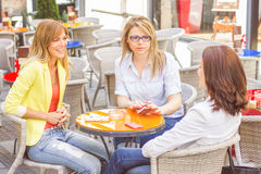 Three Young Women have Coffee Break. In street cafe Stock Photos