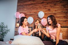 Three young women have pajama party in room on bed. They sit together and cheering with glasses of champaigne. Models stock image