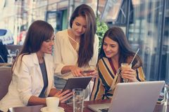 Three young women having conversation in cafe using lap top and stock photos