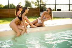 Three young women having fun by the pool. At hot summer day Royalty Free Stock Photography