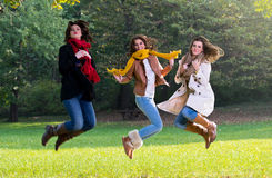 Three young women jumping joyfully in the park Stock Image