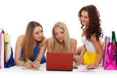 Three young women with  laptop. Shopping. Royalty Free Stock Photography