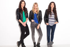 Three young women in leather jackets. Standing in studio stock photo