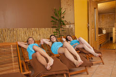 Three young women on loungers in front of sauna. Three smiling beautiful young women with towels lying on loungers in front of a sauna and posing with the thumbs royalty free stock photo