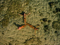 Three young women lying in sea water. Aerial view of three young women lying in sea water making a formation. Female friends relaxing in sea with their legs Royalty Free Stock Photography