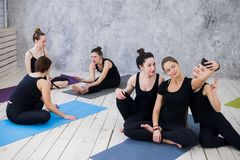 Three young women making selfie after workout at yoga class stock images