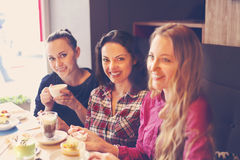 Three young women at a meeting in a cafe Stock Photography