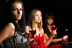 Three young women in a night bar Stock Photo