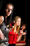 Three young fashion women in a night bar Stock Images