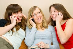 Three Young Women With Phones. Three young woman talking on phones Royalty Free Stock Image