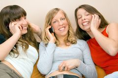 Three Young Women With Phones. Three young woman talking on phones and smiling Stock Photo