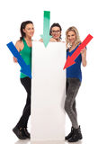 Three young women pointing arrows to a big blank board Royalty Free Stock Images
