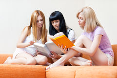 Three young women reading books. Focus on book and right woman Royalty Free Stock Image