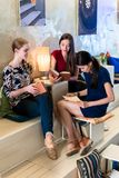 Three young women reading books in a modern location Royalty Free Stock Photos