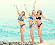Three young women on sandy beach stock photos