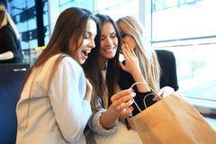 Young women sharing their new purchases with each other.They having coffee break after good shopping. Royalty Free Stock Photography