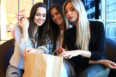 Young women sharing their new purchases with each other.They having coffee break after good shopping. Royalty Free Stock Photos