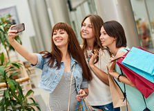 Three young women shopping at mall taking a selfie. Beautiful girls with shopping bags taking a selfie their cell phone stock photos