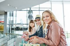 Three young women in the shopping mall stock images