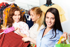 Three young women shopping together in the shop Royalty Free Stock Images