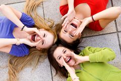 Three young women shouting. Three young girls lying down and shouting Stock Photo