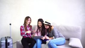 Three young women sisters use gadgets and communicate with each other, sitting on sofa in room during day. Modern and beautiful girls hold hands in their hands stock video footage