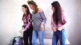 Three young women sisters use gadgets and communicate with each other, sitting on sofa in room during day. Modern and beautiful girls hold hands in their hands stock footage