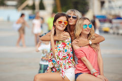 Three young women, sitting on a bench in the city Stock Images