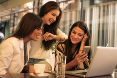 Three young woman sitting in cafe using smart phone. Three young women sitting in cafe using smart phone and having funny conversation. One of them watching on Stock Image