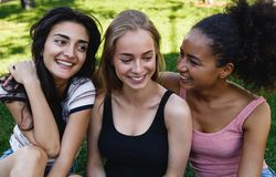 Three young women sitting in a park Royalty Free Stock Image