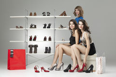 Three young women sitting trying shoes looking Royalty Free Stock Photo