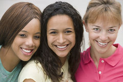 Three young women smiling, cheek to cheek, close-up, front view, portrait Royalty Free Stock Image