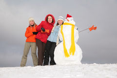 Three young women and snowman 3 Stock Images