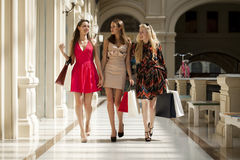 Three Young women with some shopping bags in the mall. Young beautiful women with some shopping bags walking in the mall Royalty Free Stock Images
