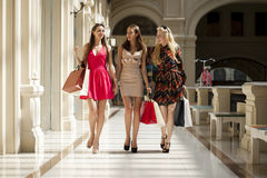 Three Young women with some shopping bags in the mall. Young beautiful women with some shopping bags walking in the mall Stock Photo