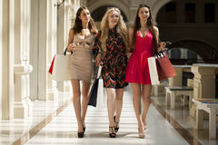 Three Young women with some shopping bags in the mall. Young beautiful women with some shopping bags walking in the mall Royalty Free Stock Photo