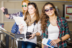 Three young women at the station or at the airport holding a camera, card, a passport, a tablet. Europeans. Stock Photography